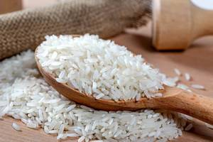 Dry white long rice in wooden spoon