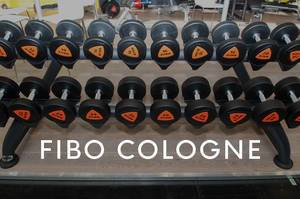 Dumbbells in various weight classes on a dumbbell rack in the gym, next to the picture title Fibo Cologne