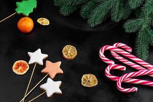 Dunkler Weihnachtshintergrund mit Lebkuchen, Mandarinen und Zuckerstangen