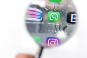 Durch Lupe fotografiertes WhatsApp Icon auf Telefon vor weißem Hintergrund