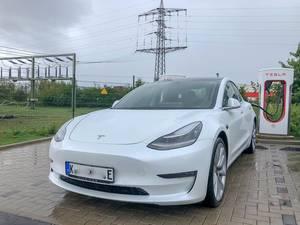 E-Mobilität: Weißer Tesla Model 3 lädt an einer Supercharger - Ladesäule bei Regenwetter