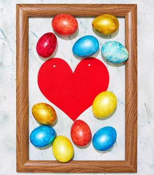 Easter concept. Colorful easter eggs placed in the wooden picture frame (Flip 2020)