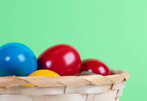 Easter eggs in a basket on green background