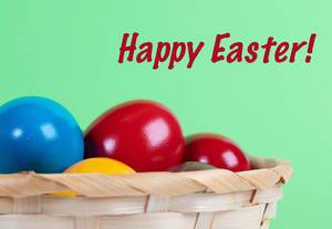 Easter eggs in a basket with Happy Easter text on green background