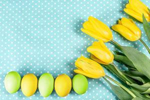 Easter eggs with yellow tulips on blue background (Flip 2020)