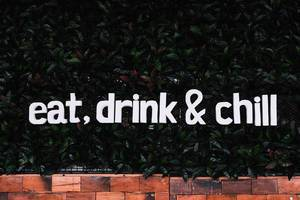 Eat drink and chill words design on a plant wall