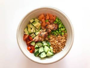 Eat Simple Daily Menu Surf & Turf Bowl with Chicken Teriyaki, sushi rice, broad beans, diced salmon and fried onions in a bowl on white table