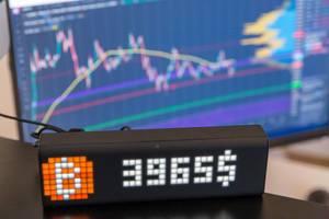 Echtzeit App Lametric zeigt den aktuellen Bitcoin Kurs mit Uhranzeige vor Computerbildschirm