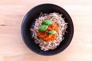 Edamama Bio-Spaghetti aus Azuki Bohnen mit Tomatensauce und Basilikumblättern auf schwarzem Teller