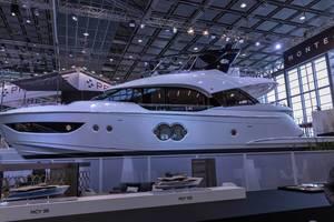 Edle Luxusyacht in Messehalle, davor Modelle von Yachten von Monte Carlo Yachts