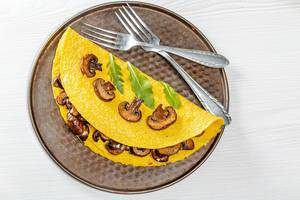 Egg omelet with mushrooms and arugula leaves and forks. Top view