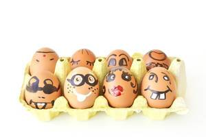 Eggs with funny faces in the packaging on white background symbolising happy easter
