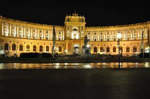 Ehemalige Kaiserresidenz und jetzt Amtssitz des österreichischen Bundespräsidenten Hofburg Wien, hell beleuchtet vor dunklem Nachthimmel