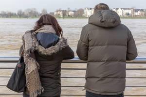 Ehepaar betrachtet den trüben Rhein