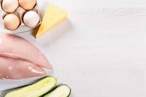 Eier, Käse, rohe Hähnchenbrust und aufgeschnittene Gurke auf einem weißen Tisch neben freiem Platz