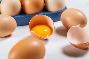 Eigelb in einer Eierschale zwischen anderen Eiern