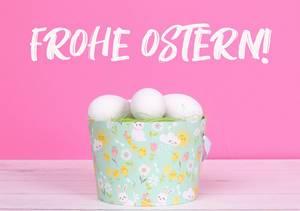 Eimer mit grünem Gras und weißen Ostereiern auf einem Holztisch vor Text Frohe Ostern auf rosa Hintergrund