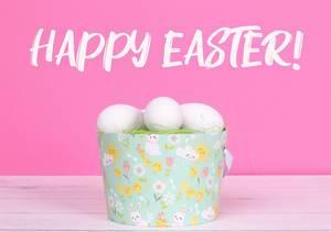 Eimer mit grünem Gras und weißen Ostereiern auf einem Holztisch vor Text Happy Easter Frohe Ostern auf rosa Hintergrund