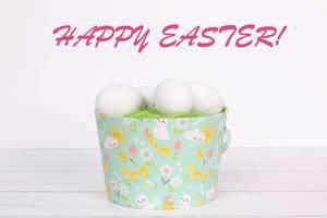 Eimer mit weißen Ostereiern und grünem Gras auf einem Holztisch mit Text Happy Easter auf weißem Hintergrund