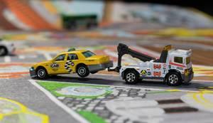 Ein Abschleppwagen schleppt ein kaputtes Taxi ab - Modelauto