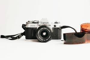 Ein alter Canon AE-1 Fotoapparat mit einem Film auf weißem Hintergrund
