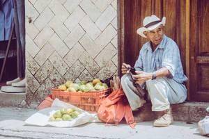 Ein alter Mann verkauft Mandarinen auf der Straße vor seinem Haus