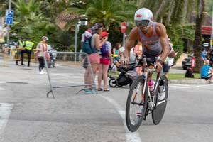 Ein Athlet mir Bart und weißem Helm schwingt sich auf das Rennrad bei einem Triathlon