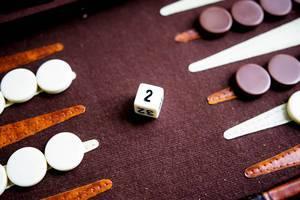 Ein Backgammon Verdoppelwürfel auf dem Spielbrett