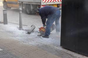 Ein Bauarbeiter schneidet mit der Steinsäge eine Auskerbung in den Gehweg