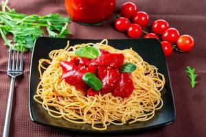 Ein Berg Spaghetti mit geschälten Tomaten und Basilikumblättern auf einem schwarzen Teller