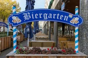 Ein Biergarten mit Holzbänken in der Innenstadt