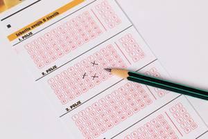 Ein Bleistift auf einem Lotterieschein mit angekreuzten Feldern