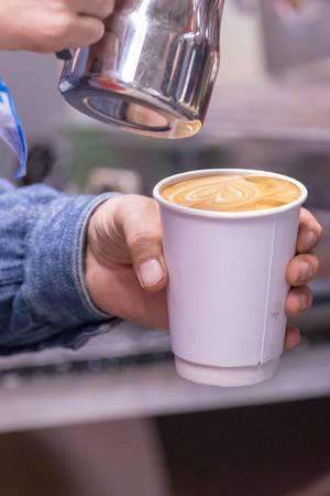 Ein Cappuccino im Pappbecher wird zubereitet