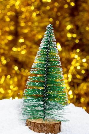 Ein dekorativer Weihnachtsbaum auf Schnee mit goldenem Lametta im Hintergrund