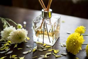 Ein Duftflakon aus Glas mit Duftstäbchen mit Blüten geschmückt