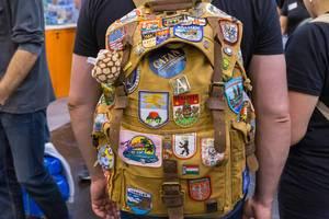 Ein Fan auf der Spielemesse trägt ein Rucksack mit vielen verschiedenen Patches