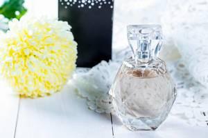 Ein Fläschchen Parfüm mit Blumen auf einem Tisch