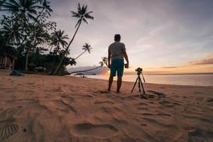 Ein Fotograf mit seinem Equipment am Strand von Punta Bulata bei Sonnenuntergang