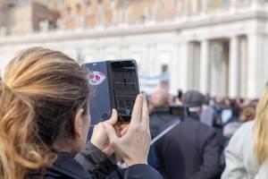 Ein Frau macht ein Foto mit dem iPhone auf dem Peterdplatz im Vatikan