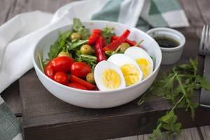 Ein frischer Rucola-Ei Salat mit Oliven, Paprika und Tomaten
