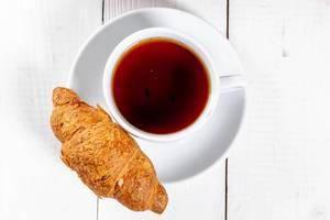 Ein frisches Croissant mit einer Tasse schwarzem Tee