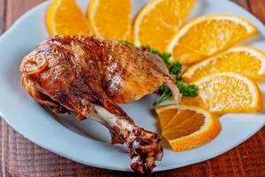 Ein gebackener Hühnchenbollen mit Orangen-Honigsoße und Orangenscheiben
