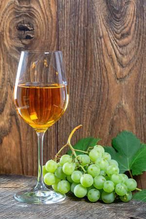 Ein gefülltes Glas Wein und Weintrauben vor einem rustikalen Holzhintergrund