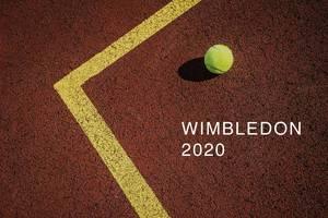 """Ein gelber Tennisball liegt auf dem Tennistunierplatz, neben der Aufschrift """"Wimbledon 2020"""""""