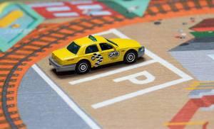 Ein gelbes Taxi auf einem Parkplatz - Modelauto