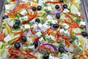 Ein gemischter Salat mit Gurken, Paprika, Zwiebeln, schwarzen Oliven, geriebenen Karotten und Feta Käse