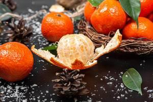 Ein geschälter Mandarin mit Zapfen, Blättern und anderen frischen Mandarinen im Hintergrund