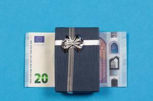Ein Geschenk auf einem 20 Euroschein auf blauem Hintergrund