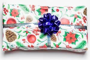 Ein Geschenk in weihnachtlichem Geschenkpapier verziert mit einer blauen Stern Schleife vor weißem Hintergrund Draufsicht
