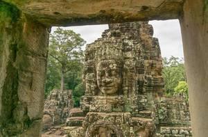 Ein Gesicht in Stein am Bayon Tempel durch ein Fenster in Siem Reap